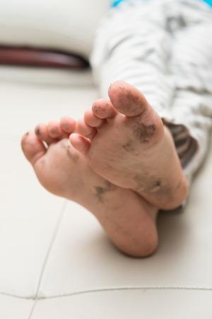 pieds sales: gar�on allong� sur le canap� avec les pieds sales