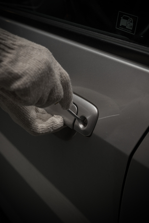 looting: car thief with glove trying to open a vehicle door by using screw driver