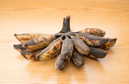 overripe: bunch of black overripe bananas on a wooden background