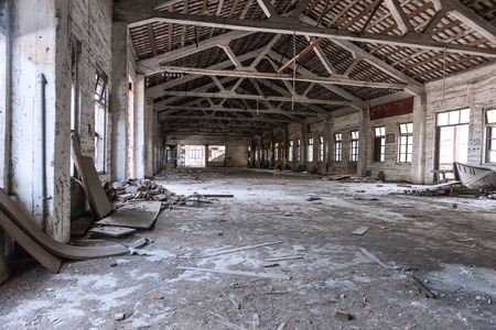 undecorated: Empty industrial loft in an architectural background with bare cement walls, floors and pillars supporting a mezzanine