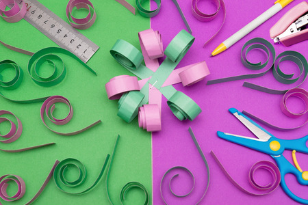 hand made flower with ruler pen scissors and stapler on colorful scrapbook Stock Photo