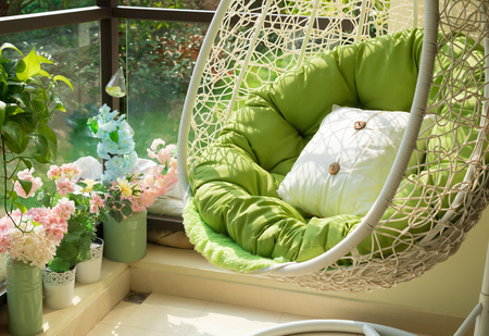 garden swing with mattress and cushion in a balcony in the morning Фото со стока