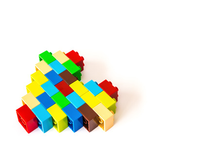 Heart made from colorful toy bricks on white with copy space