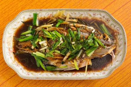 fresh steamed whole fish with herbs onions and sauce