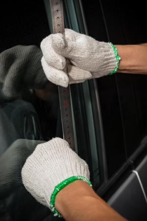 man with glove trying to open a vehicle door by steel ruler
