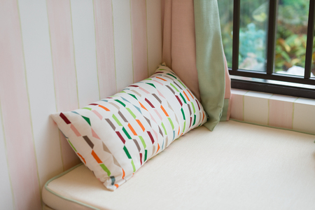resting area of a cozy window seat with cushion in the morning horizontal composition Stock Photo