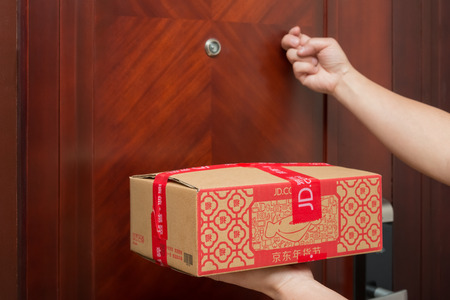 Zhongshan,China-January 25, 2017:male courier from JD.com delivering a parcel with Chinese New Year things and knocking the door.January 28 is the 1st day of year Rooster and JD.com is one of the biggest online shopping mall in China. Editorial