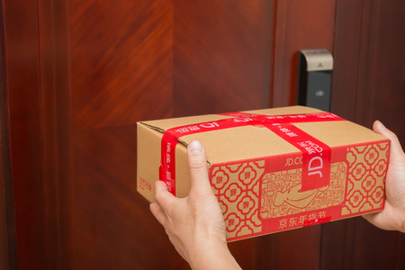 Zhongshan,China-January 25, 2017:male courier from JD.com delivering a parcel with Chinese New Year things.January 28 is the 1st day of year Rooster and JD.com is one of the biggest online shopping mall in China.