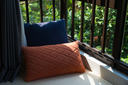 resting area of a cozy window seat with cushions in the morning horizontal composition