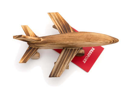 top view airplane model on top of a red passport on white background