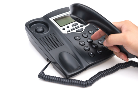 man dialing a black telephone on white background