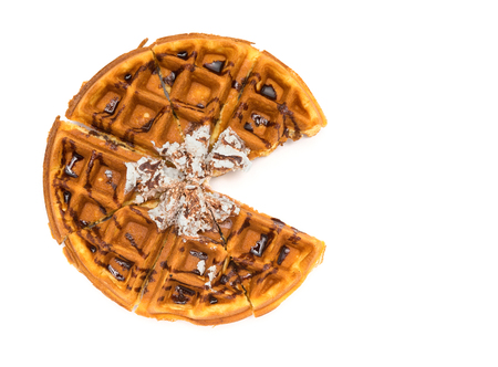 foodies: top view round waffle with one piece cut out on a white background