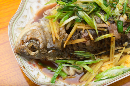 cooking oil: fresh steamed whole fish covered with herbs onions and sauce close up Stock Photo