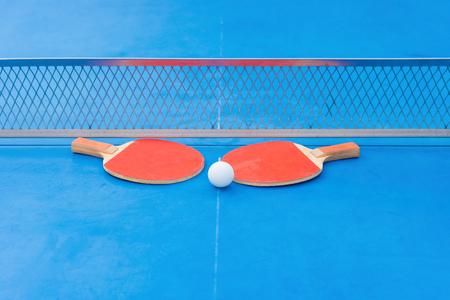 table tennis rackets and ball and net on a blue  table