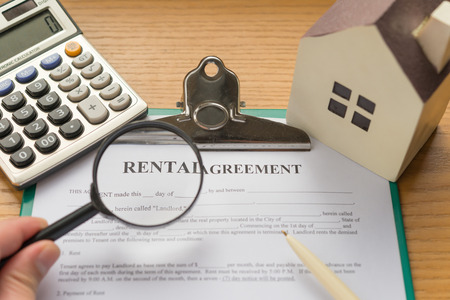rental agreement contact with an architectural model and a calculator and magnifier with rental highlighted
