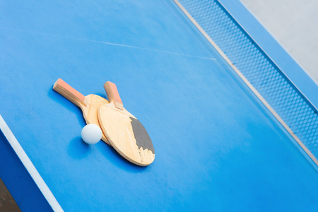 old pingpong rackets and ball and net on a blue pingpong table