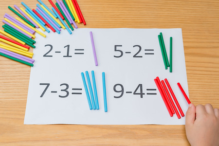kid learning simple subtraction by counting numbers of sticks