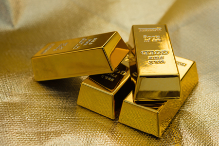four pieces of gold bars on a golden background