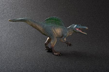 Spinosaurus toy on a dark background