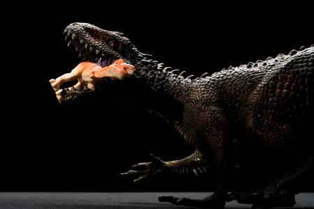 Carcharodontosaurus toy catches a smaller dinosaur on a dark background