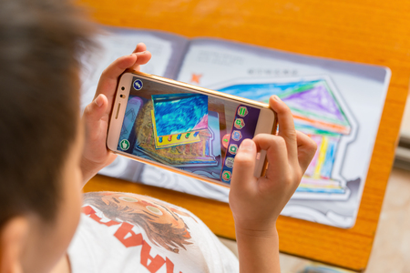 Zhongshan,China-August 8, 2017:kid playing Augmented Reality popup paintings of a filled temple via mobile. AR and VR games become more and more popular.