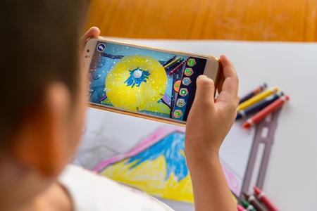 Zhongshan, China-8 de agosto de 2017: niño jugando Realidad Aumentada popup pinturas de una montaña llena a través de móvil. AR y VR juegos cada vez más popular.