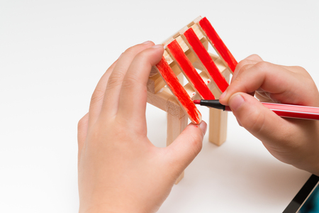 kid doing color painting for a wooden house model