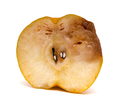 uneatable: half of a cut out rotten pear on white background