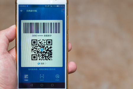 Zhongshan,China-September 2, 2017:Chinese man preparing a payment via QR code.QR code for payment and money transfering becomes very common and popular in China. Éditoriale