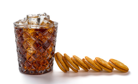 cup of iced cola and sandwich biscuits on white background