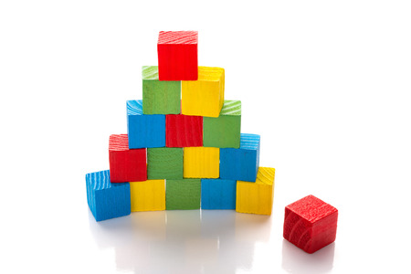 colorful wooden toy blocks stack up on a white background