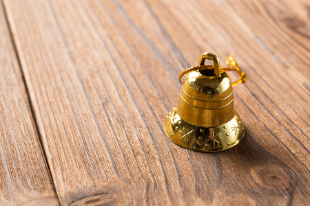 golden Christmas bell on a wood background
