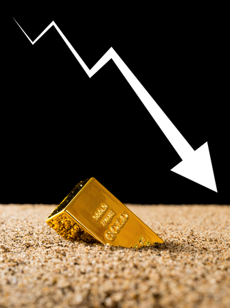 gold bar sinking into sand with a big downwards arrow on black background concept of gold price and investment Stock Photo