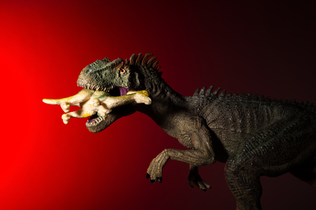 allosaurus biting a smaller dinosaur with spot light on the head and red light on background