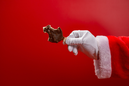 santa claus holding a chocolate flavor ice cream with some bites