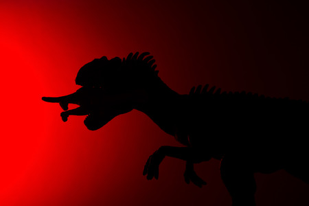 shadow of allosaurus biting a smaller dinosaur with red light in dark Stock Photo