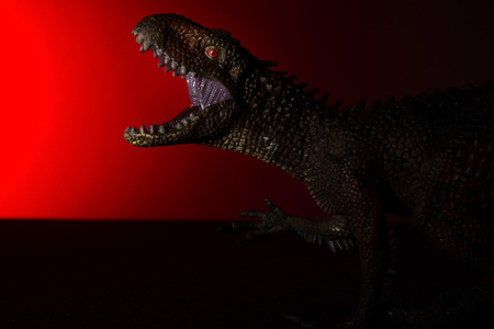 Carcharodontosaurus with spot light on the head and red light on background Stock Photo