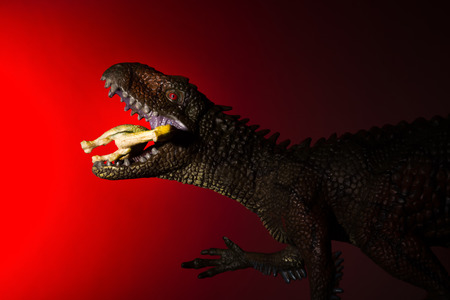 Carcharodontosaurus biting a small dinosaur with spot light on the head and red light on background