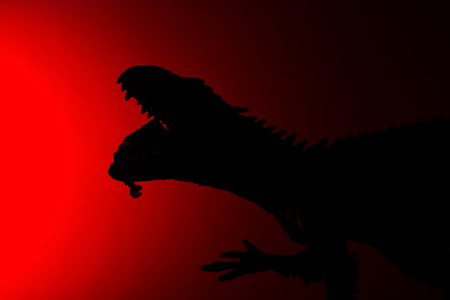 shadow of Carcharodontosaurus biting a human body with red light in dark Stock Photo