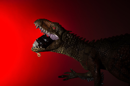 Carcharodontosaurus biting a human body with spot light on the head and red light on background