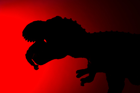 shadow of tyrannosaurus biting a human body with red light in dark Stock Photo