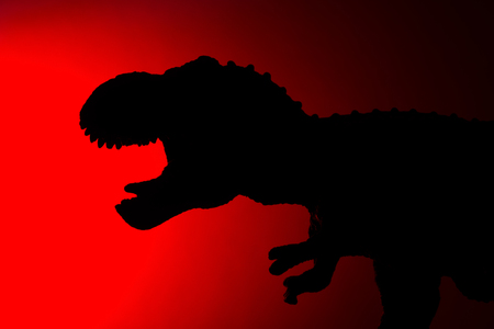 tyrannosaurus shadow with red light in dark