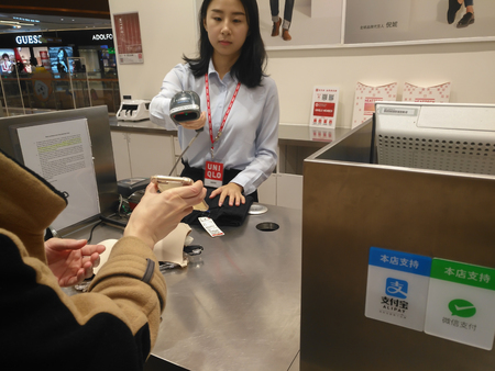 Zhongshan,China-January 1, 2018:girl doing payment at a garment retailer via mobile.Wechat or Alipay for payment and money transfering via mobile becomes very common and popular in China,fast and safe.