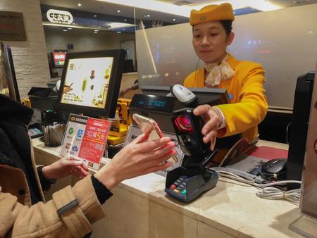 中山、中国-2018年1月1日:女の子がモバイルでレストランで支払いを行っています。モバイルを介して支払いと送金のためのWechatやアリペイは、中国で非常に一般的になり、高速かつ安全になります。