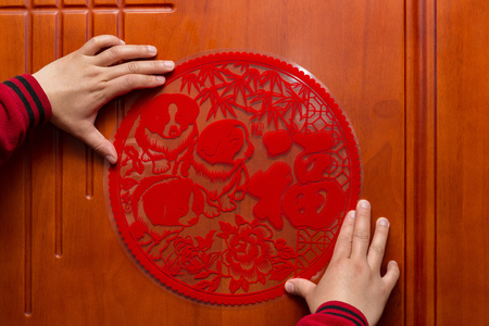 man sticking a Chinese New Year of the Dog 2018 to a door