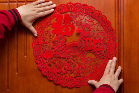 man sticking a Chinese New Year of the Dog 2018 to a door the Chinese means fortune Stock Photo