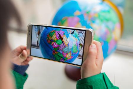 Zhongshan, Chine-7 février 2018: enfant jouant au globe contextuel de réalité augmentée avec des dinosaures via mobile. Les jeux AR et VR deviennent de plus en plus populaires.