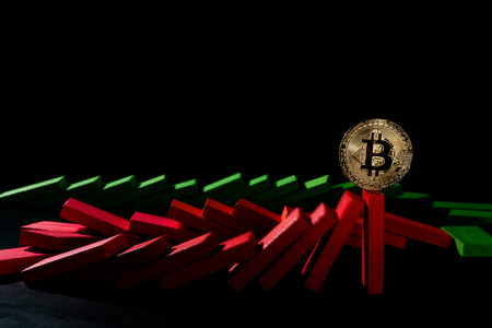 bitcoin standing on falling dominos on black background as a financial concept Stock Photo