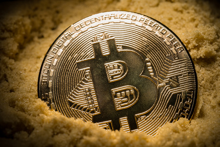 close up of bitcoin half in the sand concept of mining or price collapse