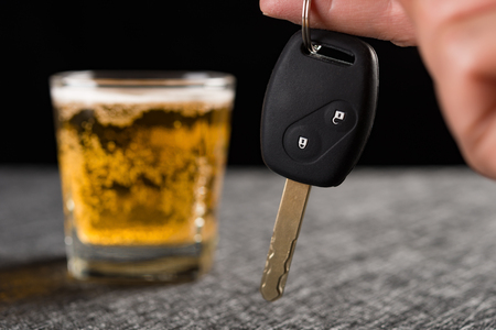 finger hold a car key in front of cup of beer concept of drunken driving Stock Photo